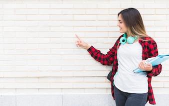 Glimlachende vrouwelijke universitaire studentenholding boeken die ter beschikking de vinger op witte geschilderde muur richten