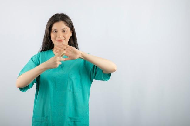 Glimlachende vrouwelijke verpleegster die haar hand op wit bespuit.