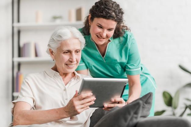 Glimlachende vrouwelijke verpleegster en haar patiënt die het digitale tabletscherm bekijken