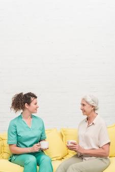 Glimlachende vrouwelijke verpleegster en hogere de koffiekop die van de vrouwenholding elkaar bekijken