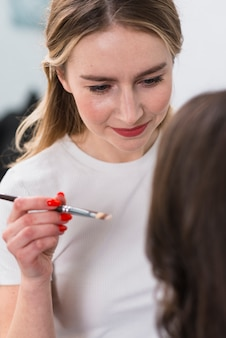 Glimlachende vrouwelijke visagiste die make-up toepast
