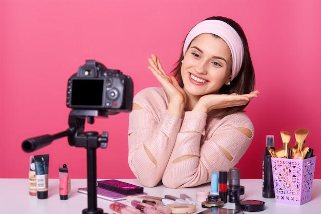 Glimlachende vrouwelijke vlogger maakt nieuwe video-inhoud, zit voor camera, omringd met cosmetische producten, draagt hoofdband, geïsoleerd over roze