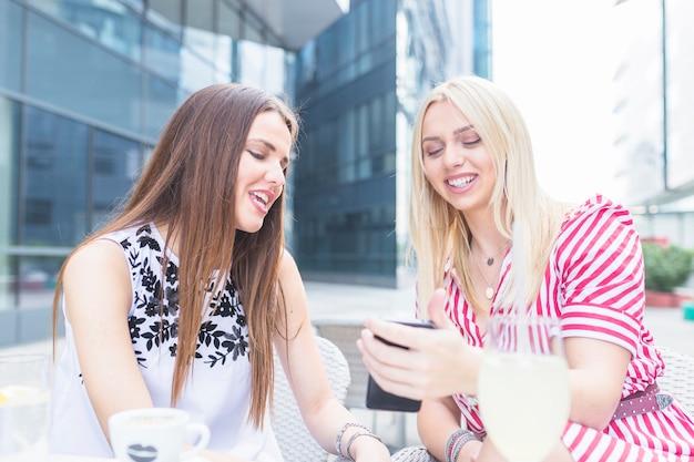 Glimlachende vrouwelijke vrienden die mobiele telefoon bekijken