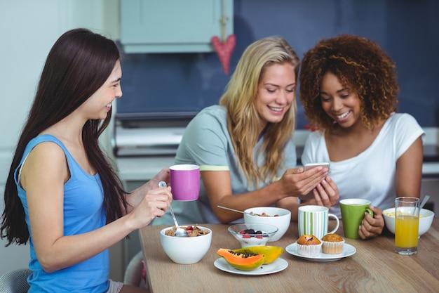 Glimlachende vrouwelijke vrienden die smartphone gebruiken