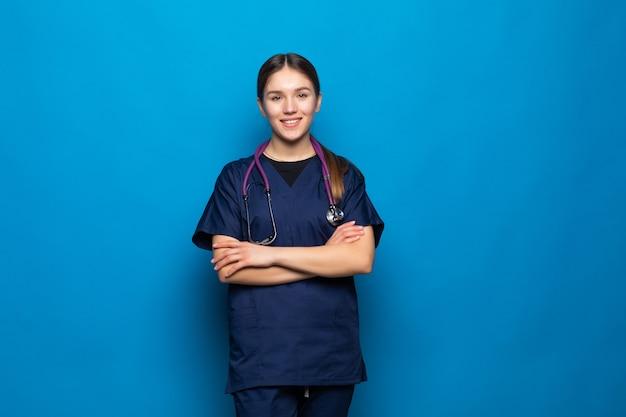 Glimlachende vrouwelijke vrouwelijke arts op blauw