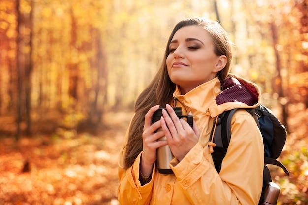Glimlachende vrouwelijke wandelaar heeft een pauze voor warme dranken
