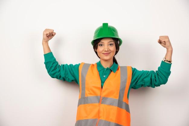 Glimlachende vrouwelijke werknemer die haar spieren toont Gratis Foto