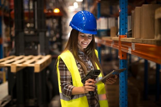 Glimlachende vrouwelijke werknemer die tablet en streepjescodescanner houdt die inventaris in distributiemagazijn controleert