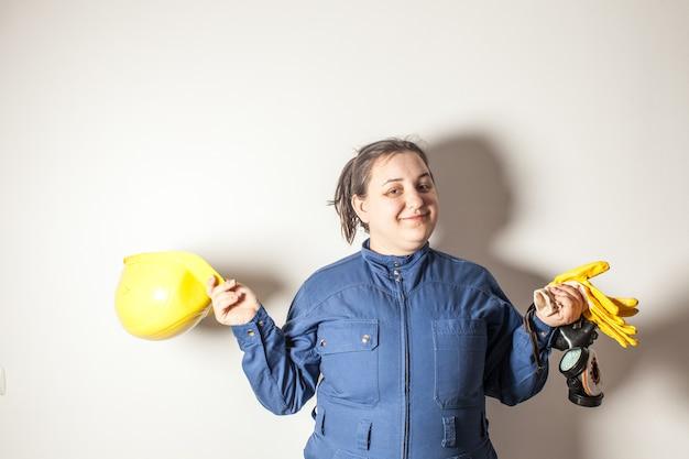 Glimlachende vrouwelijke werknemer gekleed in werkkleding, met een gele helm en gele handschoenen