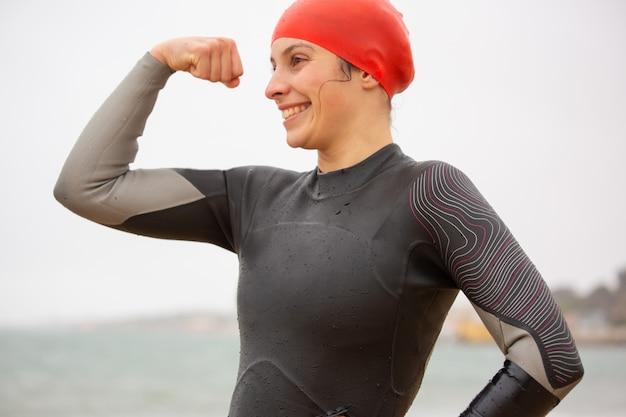 Glimlachende vrouwelijke zwemmer die bicepsen toont