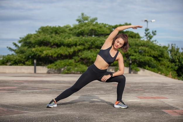 Glimlachende vrouwen aziatische atleet die uitrekkende oefening doet, die voor ochtendtraining en levensstijlconcept op stad voorbereidingen treft