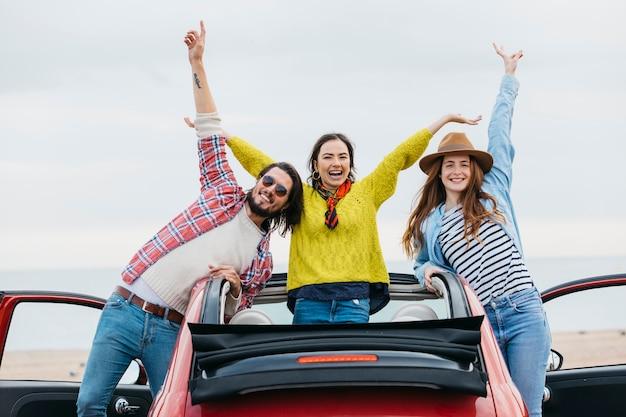 Glimlachende vrouwen dichtbij de gelukkige mens met upped handen die uit auto leunen