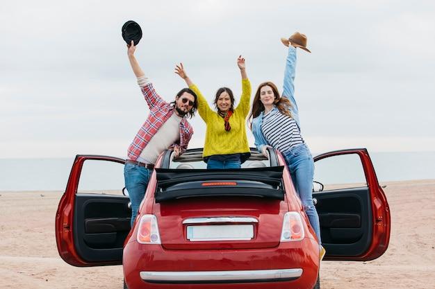 Glimlachende vrouwen dichtbij de mens met upped handen die uit van auto op kust leunen