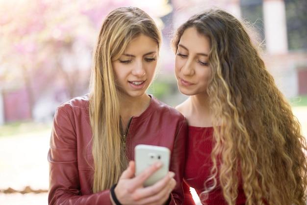 Glimlachende vrouwen die een mobiele telefoon met behulp van