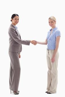 Glimlachende vrouwen die handen schudden