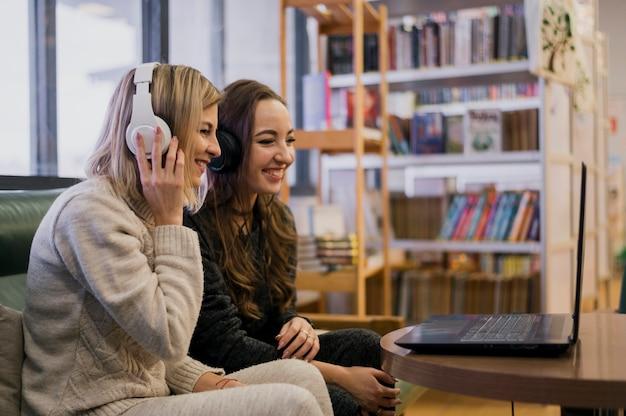 Glimlachende vrouwen die hoofdtelefoons dragen die laptop bekijken