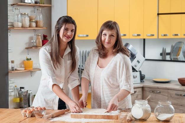 Glimlachende vrouwen die in familiekeuken stellen