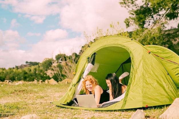 Glimlachende vrouwen die in tent met laptop liggen