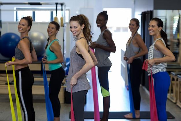 Glimlachende vrouwen die rekoefening met weerstandsband uitvoeren