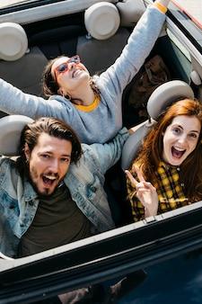 Glimlachende vrouwen en positieve man zitten in de auto