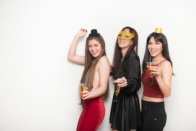 Glimlachende vrouwen in avondkleding met glazen dranken