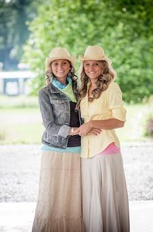 Glimlachende vrouwen in hoeden en kleurrijke jurken in een park onder zonlicht