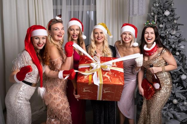 Glimlachende vrouwen met een groot cadeau thuis bij de kerstboom