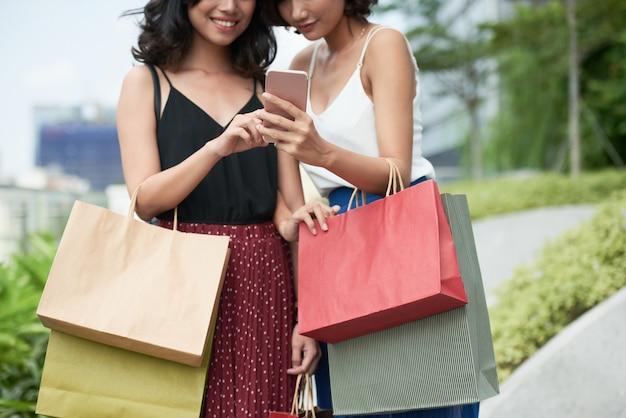 Glimlachende vrouwen met smartphone