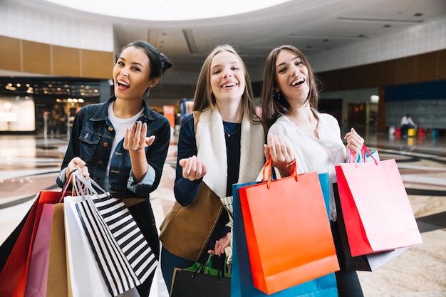 Glimlachende vrouwen met zakken gebaren op camera