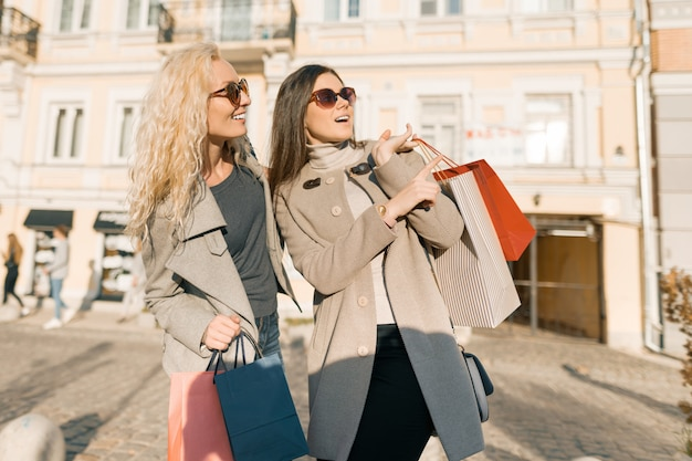 Glimlachende vrouwen op een stadsstraat met het winkelen zakken