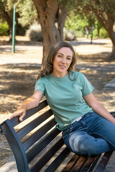 Glimlachende vrouwen van middelbare leeftijd die een t-shirt en spijkerbroek dragen en op de bank in het park zitten
