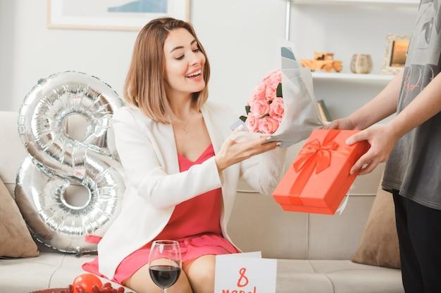 Glimlachende vrouwen zittend op de bank op gelukkige vrouwendag geeft cadeau met boeket door iemand in de woonkamer