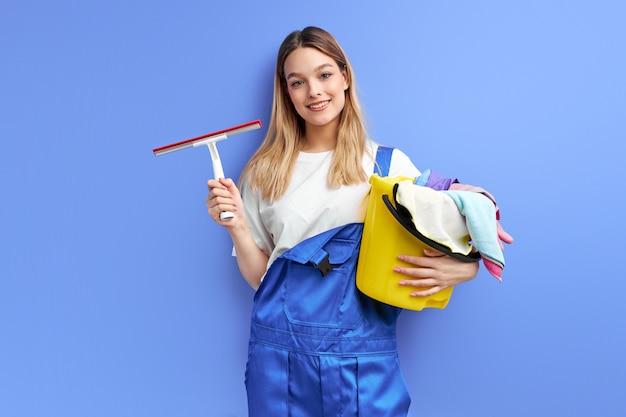 Glimlachende vrouwenhuisvrouw die in handschoenen reinigingsmiddel dingen houden die over purpere studioachtergrond worden geïsoleerd.