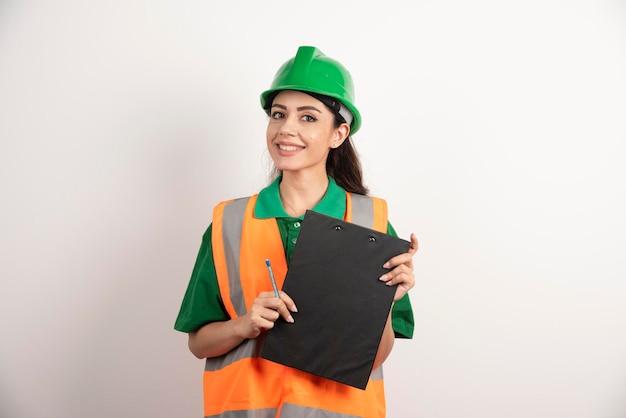 Glimlachende vrouweningenieur die klembord op witte achtergrond houdt. hoge kwaliteit foto