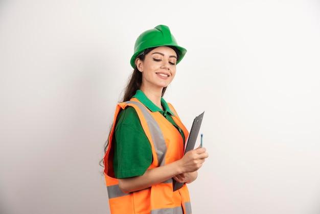 Glimlachende vrouweningenieur die met klembord neer op witte achtergrond kijken