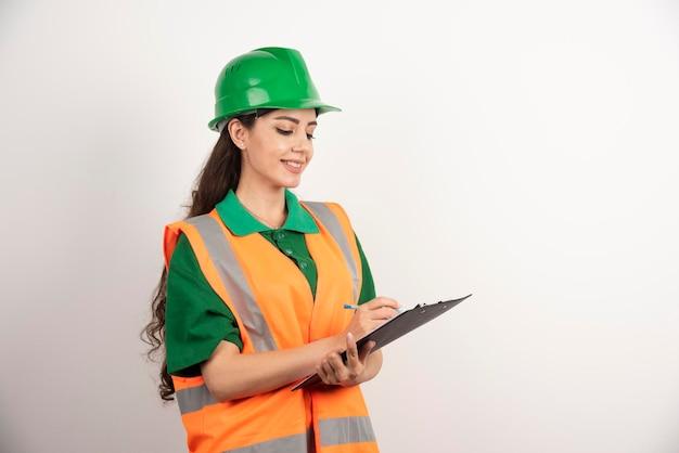 Glimlachende vrouweningenieur die op klembord op witte achtergrond kijken