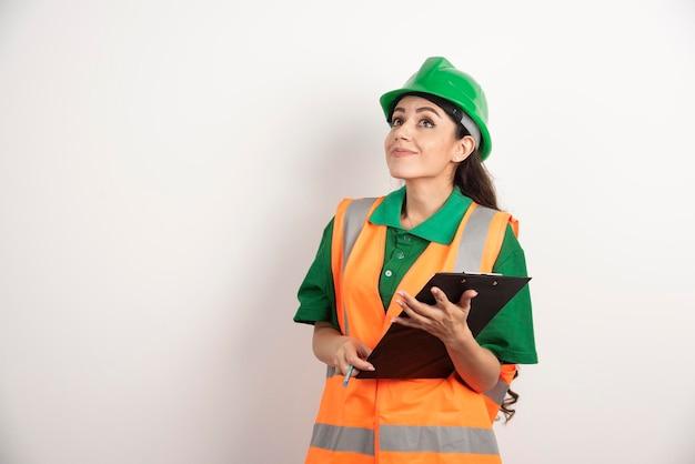 Glimlachende vrouweningenieur met klembord op witte achtergrond. hoge kwaliteit foto
