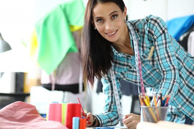 Glimlachende vrouwenkleermaker op workshopportret.