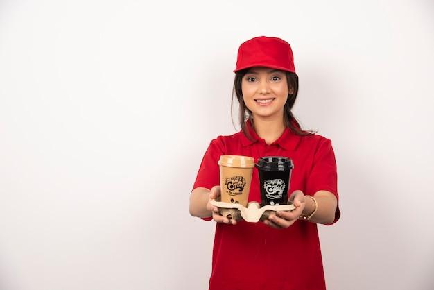 Glimlachende vrouwenkoerier die koffie voor levering op witte achtergrond houdt.