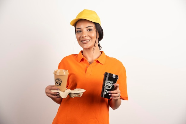 Glimlachende vrouwenkoerier die twee koppen koffie aanbiedt