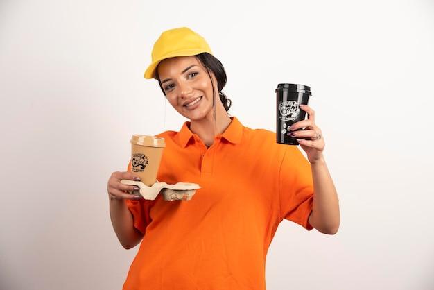 Glimlachende vrouwenkoerier die twee koppen koffie geeft