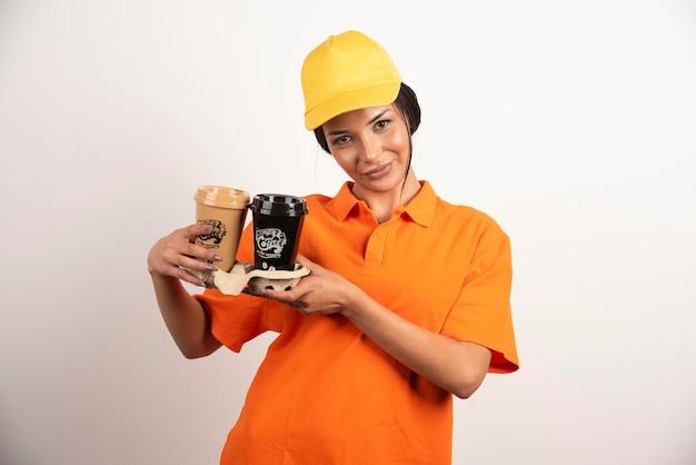 Glimlachende vrouwenkoerier die twee koppen koffie houdt