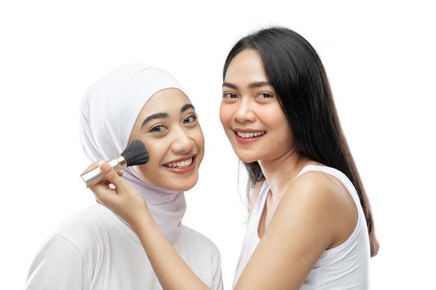 Glimlachende vrouwenmake-upkunstenaar die wang met borstel van jonge moslimvrouw in sluier toepast