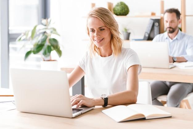 Glimlachende vrouwenmanager die aan laptop computer werkt