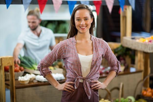 Glimlachende vrouwenverkoper die zich in de kruidenierswinkelopslag bevinden met handen op heupen