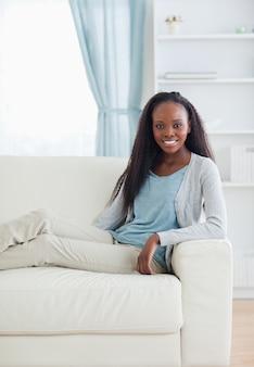 Glimlachende vrouwenzitting met haar benen op bank