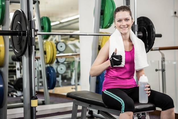 Glimlachende vrouwenzitting op barbellbank en het tonen van duim omhoog bij de gymnastiek