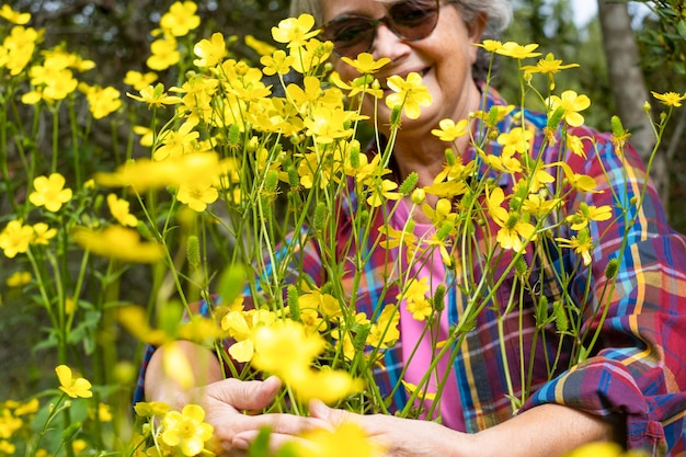 Glimlachende wazige vrouw knuffelt een groep gele bloemen in de wei