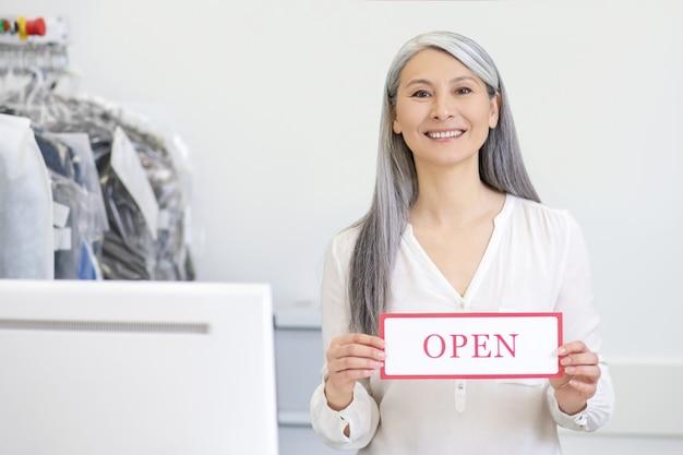 Glimlachende welwillende langharige vrouw achter stomerij teller bedrijf teken open