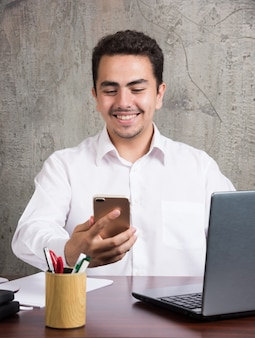 Glimlachende werknemer die telefoon onderzoekt en aan de balie zit. hoge kwaliteit foto